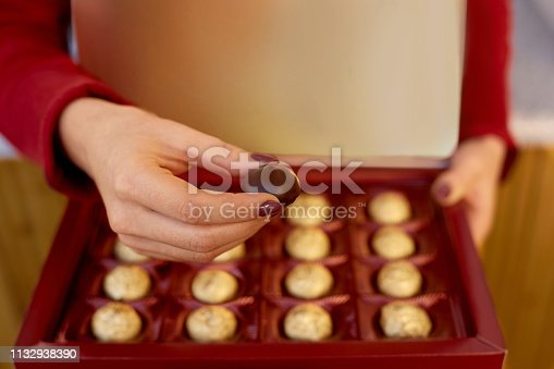 Young woman holding heart box with candies . Happy valentines gift concept