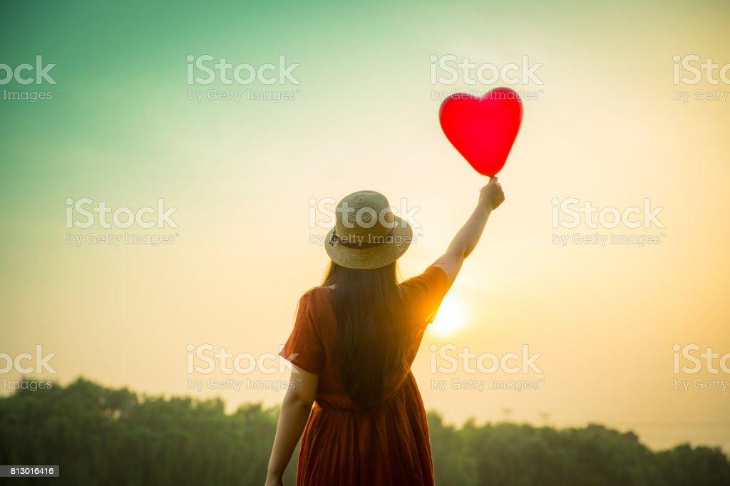 ハートのバルーンを保持している若い女性 - お祝いのロイヤリティフリーストックフォト