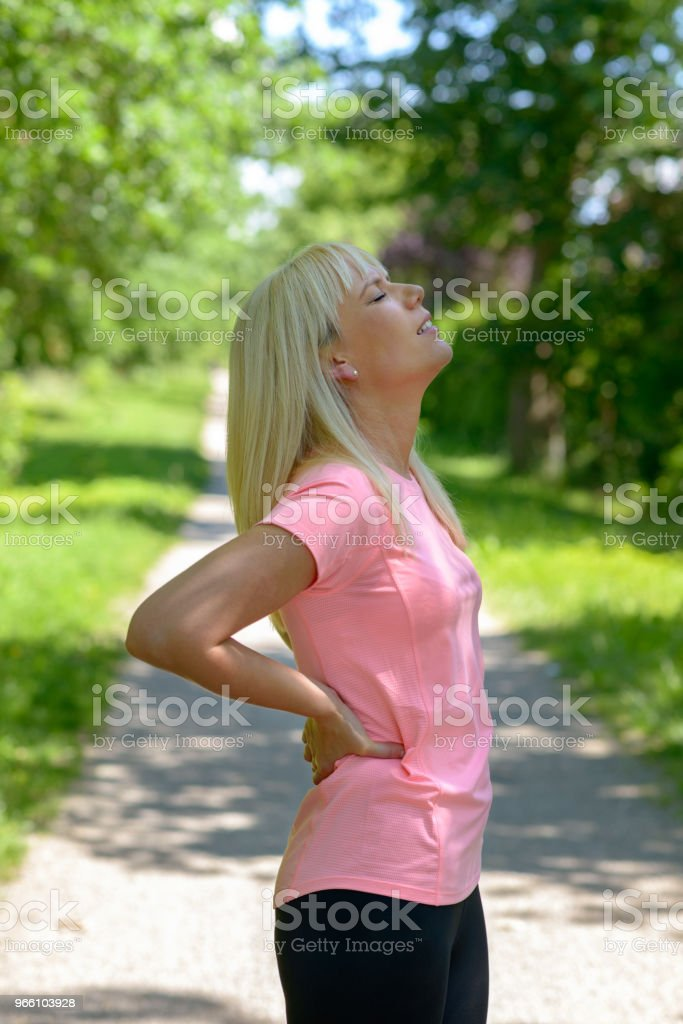 Young woman holding her lower back - Royalty-free Adult Stock Photo