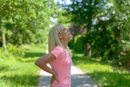 Young Woman Holding Her Lower Back - Fotografias de stock e mais imagens de Adulto
