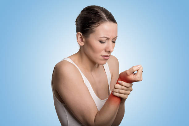 Young woman holding her painful wrist over blue background. Sprain pain location indicated by red spot. stock photo