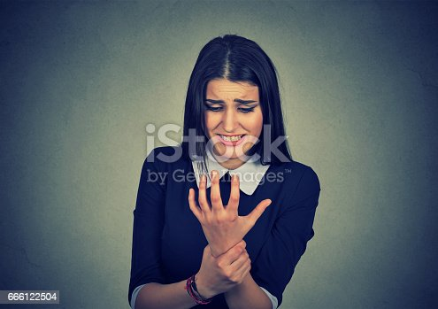 istock Young woman holding her painful wrist 666122504