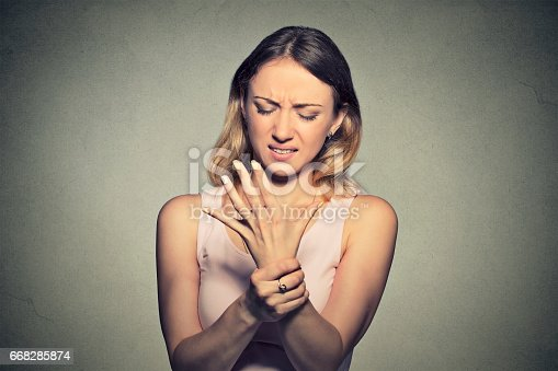 668285874istockphoto Young woman holding her painful wrist 668285874