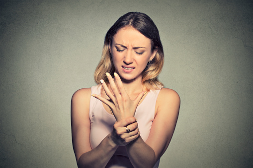 istock Young woman holding her painful wrist 668285874