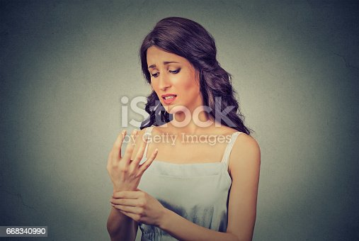 istock Young woman holding her painful wrist 668340990