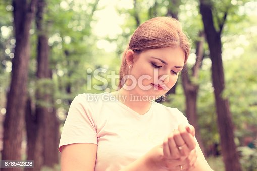 668285874istockphoto Young woman holding her painful wrist 676542328