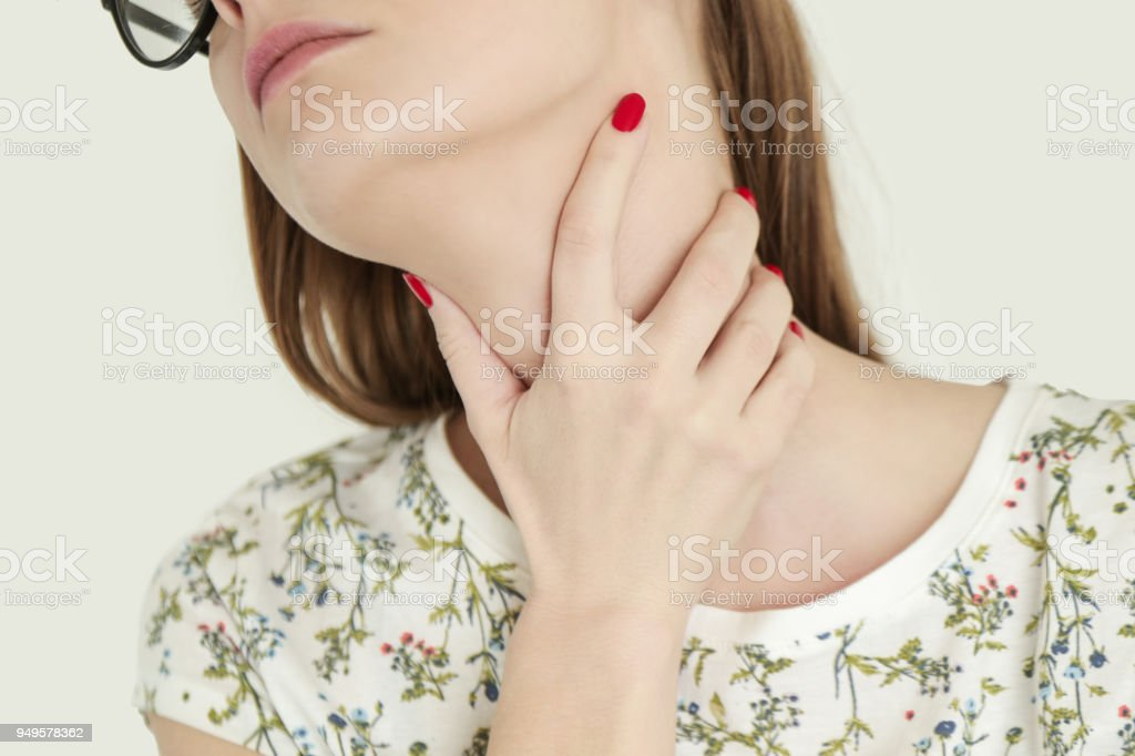 Young woman holding her throat, Sore throat, stock photo