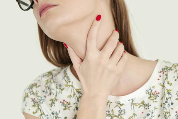Junge Frau mit ihrem Hals, Halsschmerzen, – Foto
