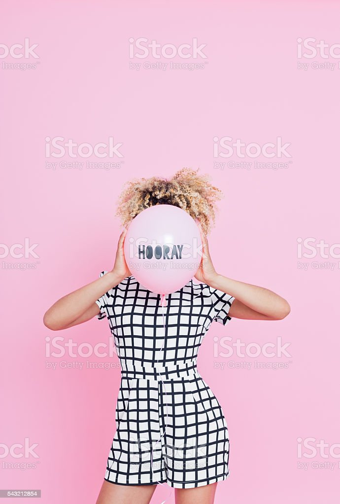 Young woman holding HOORAY balloon Portrait of unrecognisable young woman, wearing grid check playsuit, standing against pink background and hide her face behind HOORAY Balloon. 2016 Stock Photo