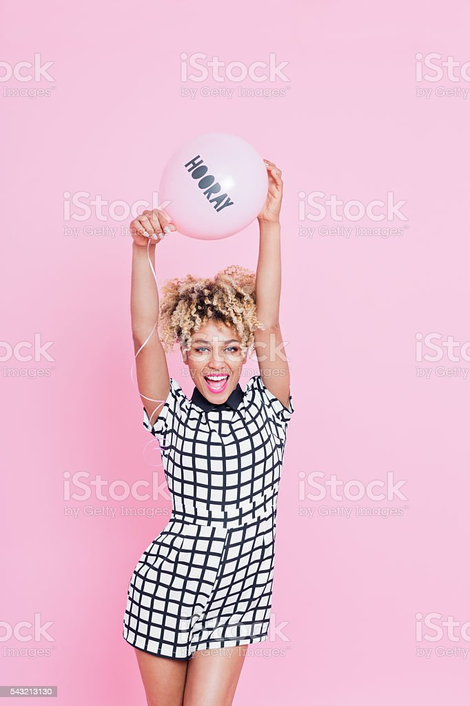 Young woman holding HOORAY balloon Portrait of young woman, wearing grid check playsuit, standing against pink background and holding HOORAY Balloon above here head. 20-29 Years Stock Photo