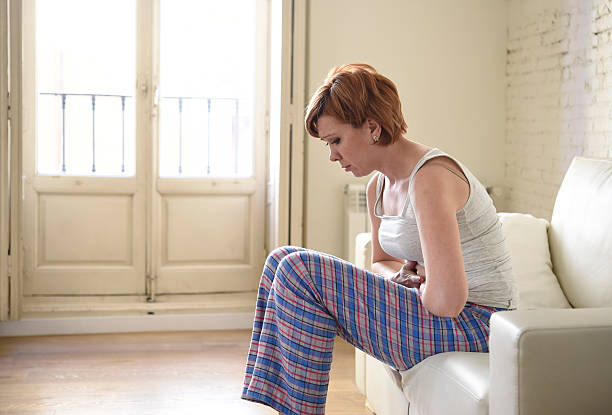 young woman holding hurting belly suffering stomach cramp  period pain stock photo