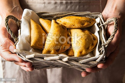 Young woman holding in hands wicker basket with freshly baked empanadas turnover pies with vegetables cheese in tomato sauce. Knfolk style. Cozy authentic atmosphere.