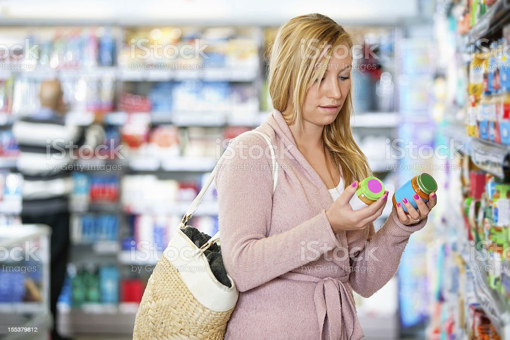 Young woman holding jar in the supermarket stock photo