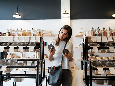 A young latin woman standing and holding two jars in a zero waste store.