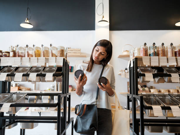Young woman holding jars in zero waste store stock photo