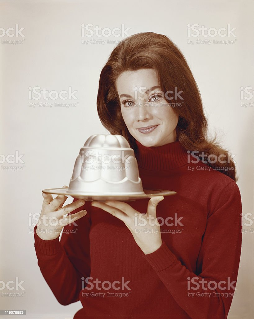 Young woman holding jelly mould, smiling, portrait stock photo