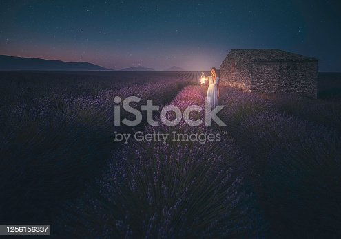 The girl with blue dress walking while holds a large old classic kerosene oil or gas lamp in the dark area of endless lavenders field under stars at night in Valensole, Provence, France
