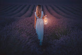 istock Young woman holding lantern in the lavender field during night 1256156376