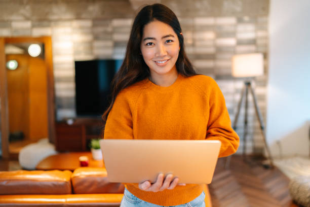 Young woman holding laptop and smiling for camera stock photo