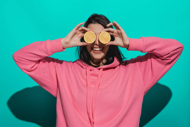 young woman holding lemon while standing by a blue color background - milan2099 stock photos and pictures