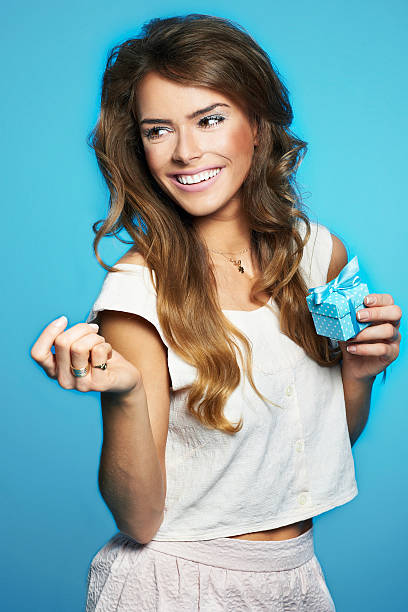 Young woman holding little present wrapped in blue stock photo