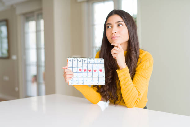 young woman holding menstruation calendar serious face thinking about question, very confused idea - mestruazione foto e immagini stock