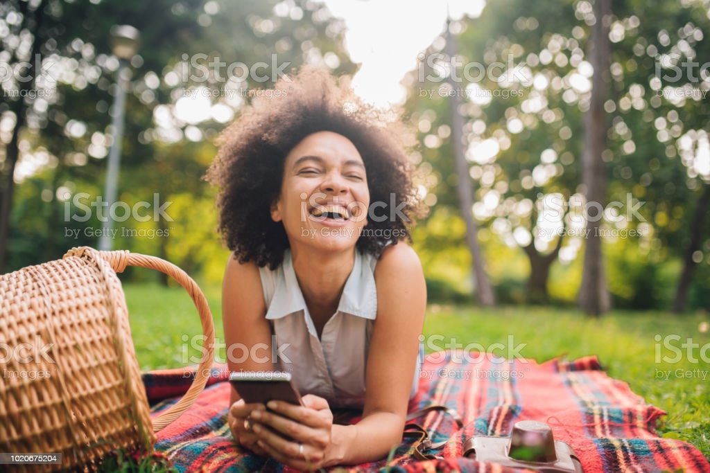 Young woman smiling and using mobile phone while being on picnic in...