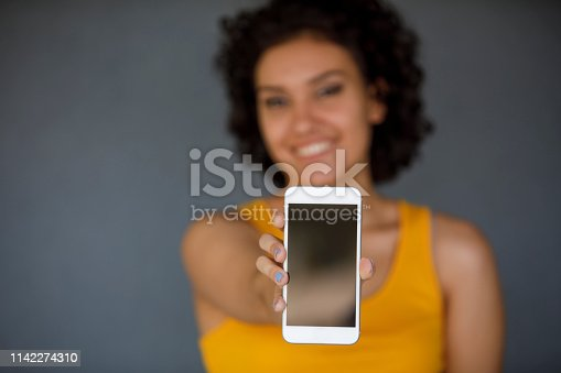 1132512623istockphoto Young woman holding mobile phone 1142274310
