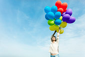 Young woman holding multi colored balloons, hands up. Cloudy sky as background.