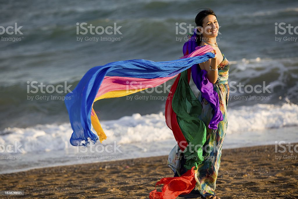 Young woman holding multicolored silk shawls stock photo