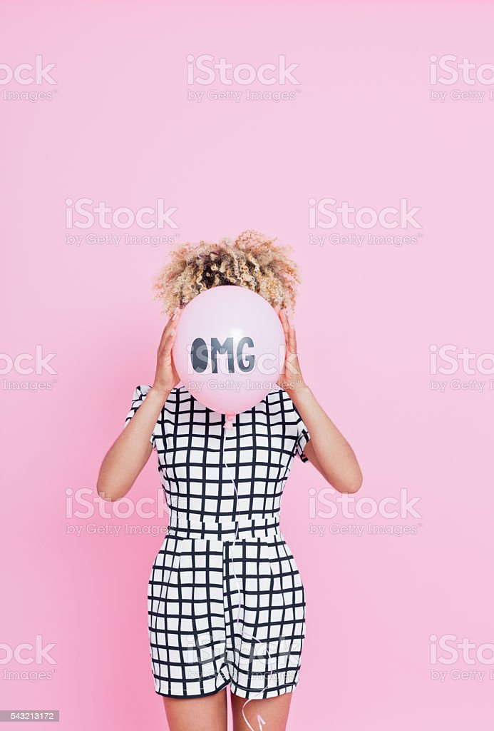 Young woman holding OMG balloon Portrait of unrecognisable young woman, wearing grid check playsuit, standing against pink background and hide her face behind OMG Balloon. 2016 Stock Photo