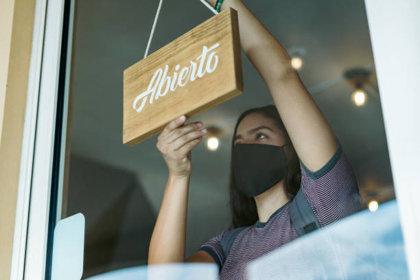 Young woman holding open sign in small business stock photo