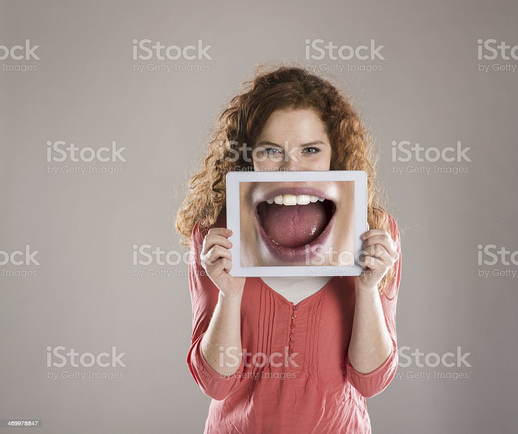 Young woman holding oversized picture of an open mouth stock photo