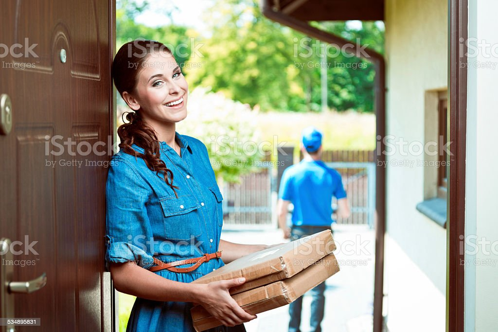 Young woman holding packages Young woman standing at the entrance door and holding parcels in hands, smiling at camera. Delivery man in the background. 2015 Stock Photo