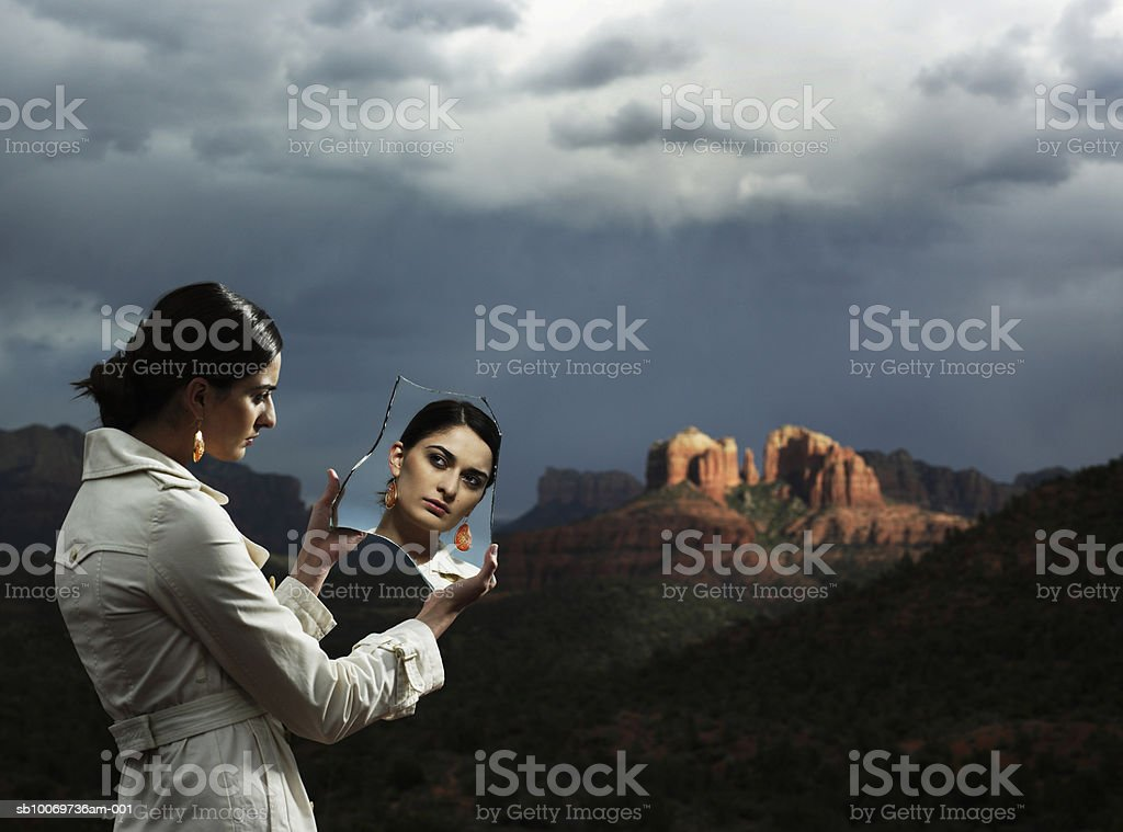 Young woman holding piece of broken mirror at dusk royalty-free stock photo