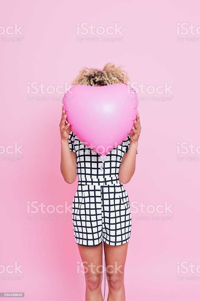 Young woman holding pink heart shaped balloon Portrait of unrecognisable young woman, wearing grid check playsuit, standing against pink background and covering her face behind Pink Heart Balloon. 2016 Stock Photo