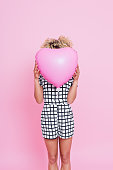 Portrait of unrecognisable young woman, wearing grid check playsuit, standing against pink background and covering her face behind Pink Heart Balloon.