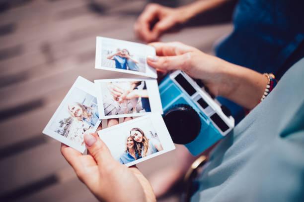Jovem mulher segurando fotos polaroid com a mãe em férias de verão - foto de acervo