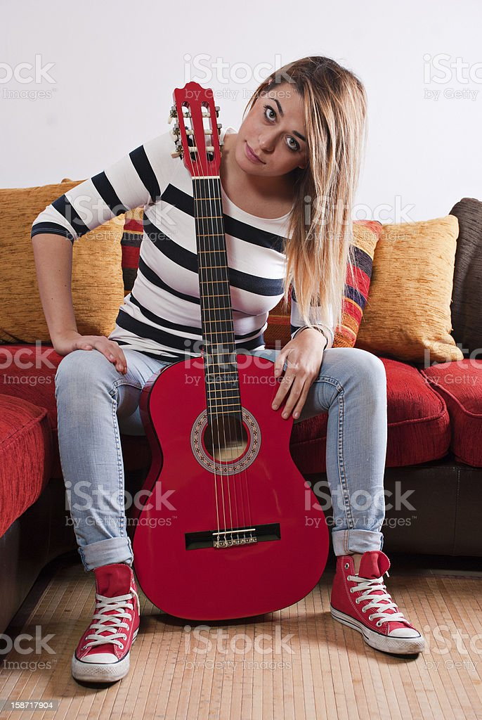 Young woman holding red guitar. royalty-free stock photo