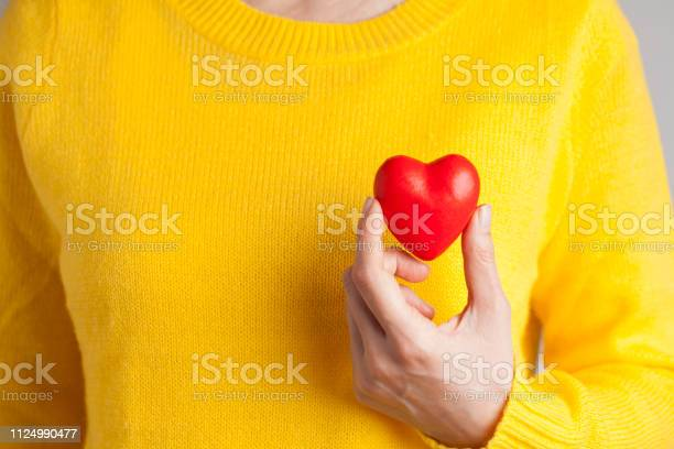 Photo of Young woman holding red heart, health insurance, donation, love concept