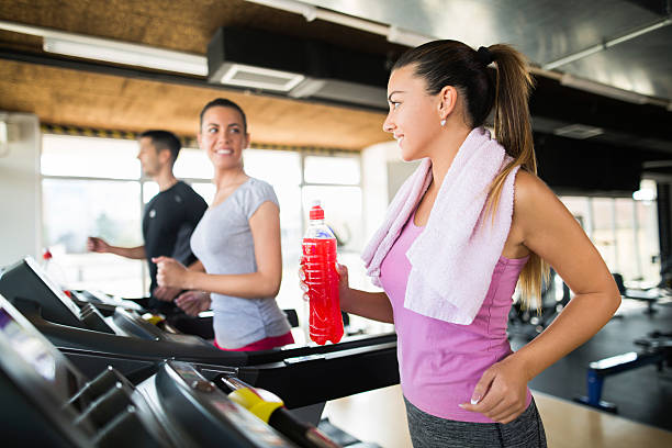 Young woman holding refreshment drink while exercising on treadmill. - foto de acervo