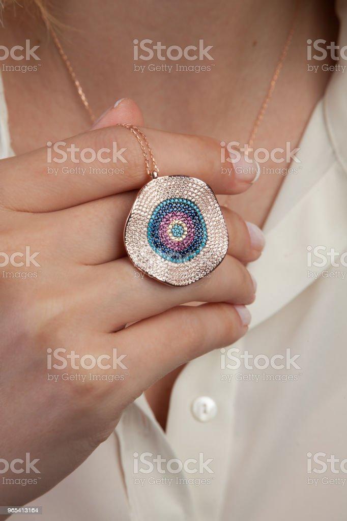 Jeune femme tenant Or Rose collier de mauvais œil - Photo de Accessoire libre de droits