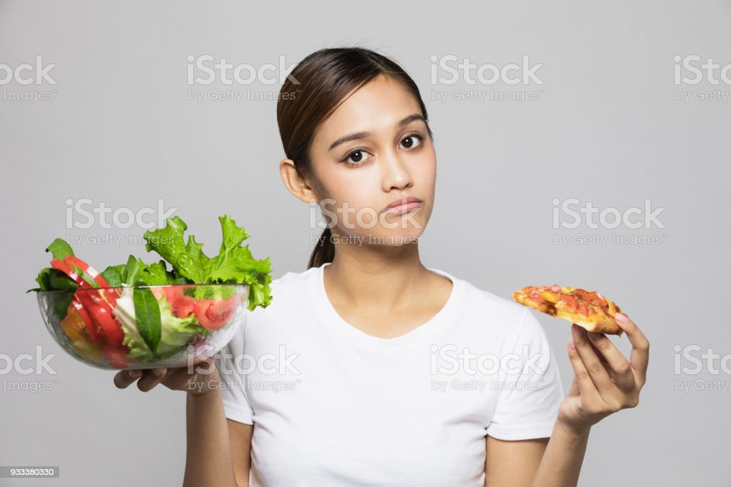 Young woman holding salad bowl and pizza. stock photo