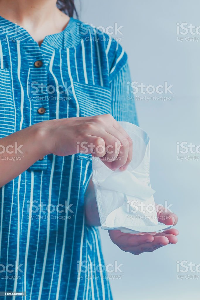 Young woman holding sanitary napkins. Period days concept showing...