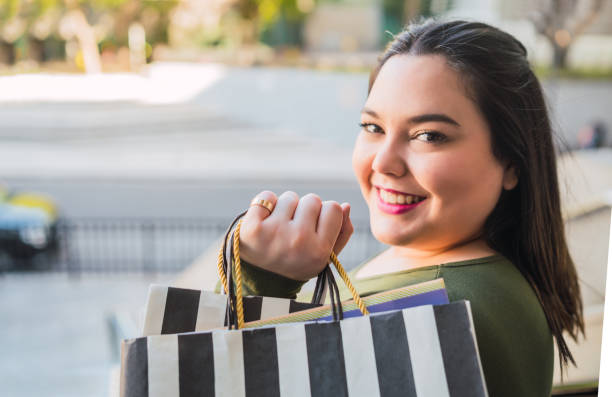 Young woman holding shopping bags at mall. stock photo