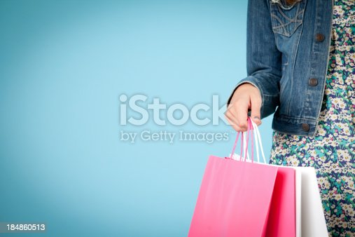 Color image of a young woman holding her shopping bags, with room for your text.