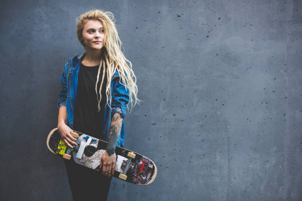 young woman holding skateboard outdoors, against grey wall - skateboard stock pictures, royalty-free photos & images