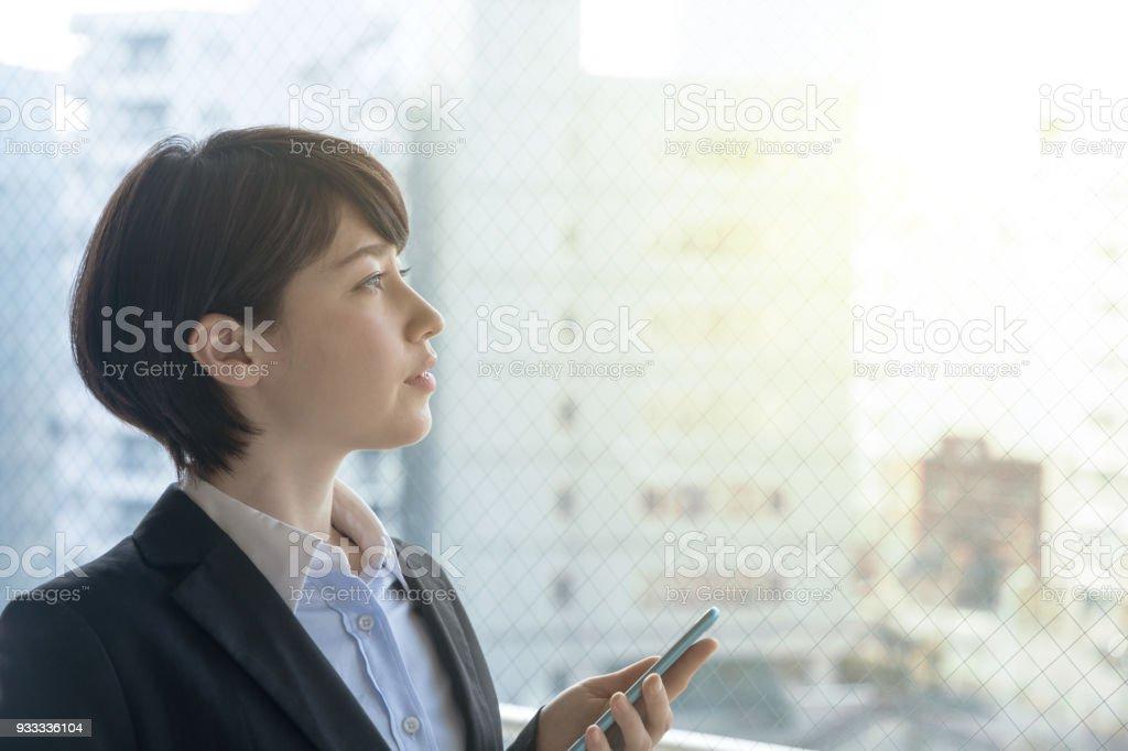 オフィスでスマート フォンを保持している若い女性。 ストックフォト