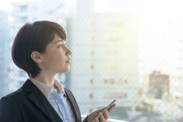 Young woman holding smart phone in the office. stock photo
