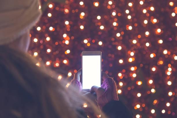 junge frau holding smartphone. roten bokeh im hintergrund. - weihnachtsprogramm stock-fotos und bilder